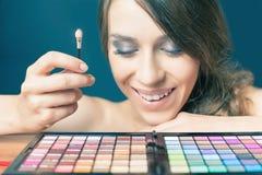 Lycklig kvinna med den färgrika paletten för modemakeup Royaltyfria Foton