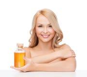Lycklig kvinna med den olje- flaskan arkivfoton