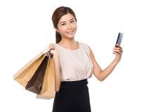 Lycklig kvinna med den shoppingpåsen och mobiltelefonen Arkivfoto