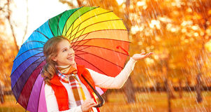 Lycklig kvinna med det mångfärgade paraplyet för regnbåge under regn i medeltal Royaltyfri Bild