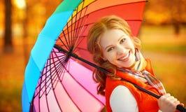 Lycklig kvinna med det mångfärgade paraplyet för regnbåge under regn i medeltal Royaltyfria Foton