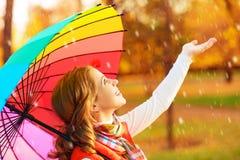 Lycklig kvinna med det mångfärgade paraplyet för regnbåge under regn i medeltal Royaltyfria Bilder
