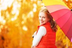 Lycklig kvinna med det mångfärgade paraplyet för regnbåge under regn i medeltal Arkivfoto