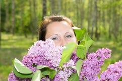 Lycklig kvinna med en bukett av blommor som ler i parkera Royaltyfri Bild