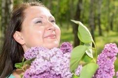 Lycklig kvinna med en bukett av blommor som ler i parkera Arkivfoto