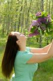 Lycklig kvinna med en bukett av blommor som ler i parkera Royaltyfri Foto