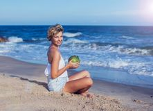 Lycklig kvinna med en kokosnöt på stranden royaltyfri fotografi