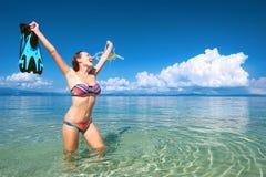 Lycklig kvinna med en maskering för att snorkla på en bakgrund av blått s Royaltyfri Foto