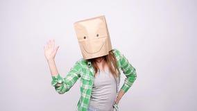 Lycklig kvinna med en pappers- påse på hennes head dans lager videofilmer