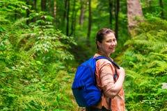 lycklig kvinna med en ryggsäck som igenom strosar Arkivfoto