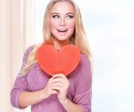 Lycklig kvinna med en stor röd hjärta Royaltyfria Bilder