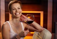 Lycklig kvinna med ett exponeringsglas av vin Royaltyfria Bilder