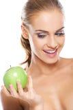 Lycklig kvinna med ett knaprigt grönt äpple arkivbilder