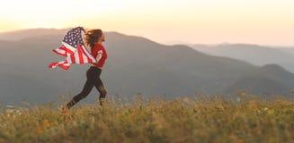 Lycklig kvinna med flaggan av Förenta staterna som tycker om solnedgången på na Arkivbild