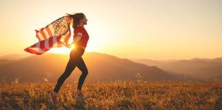Lycklig kvinna med flaggan av Förenta staterna som tycker om solnedgången på na arkivfoton