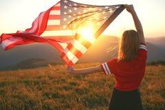 Lycklig kvinna med flaggan av Förenta staterna som tycker om solnedgången på na royaltyfria foton