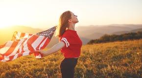 Lycklig kvinna med flaggan av Förenta staterna som tycker om solnedgången på na fotografering för bildbyråer