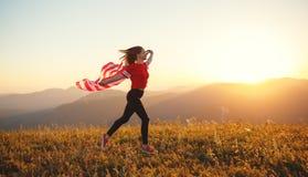 Lycklig kvinna med flaggan av Förenta staterna som tycker om solnedgången på na royaltyfri foto