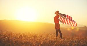 Lycklig kvinna med flaggan av Förenta staterna som tycker om solnedgången på na royaltyfria bilder