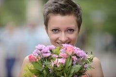 Lycklig kvinna med gruppen av blommor Arkivbild