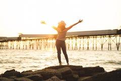 Lycklig kvinna med händer upp anseende på solnedgångstranden i sommarintelligens arkivfoto