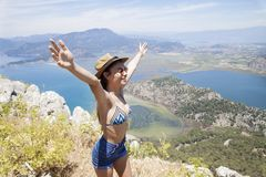 Lycklig kvinna med händer upp att stå på klippan över havet och öar på sommar Tappninglynne, begrepp av vinnaren, frihet, lycka e fotografering för bildbyråer