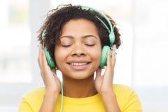 Lycklig kvinna med hörlurar som lyssnar till musik royaltyfria bilder
