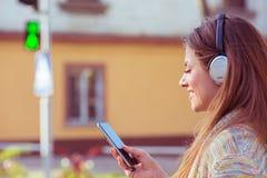 Lycklig kvinna med hörlurar som lyssnar till musik på mobiltelefonen som går korsningen gata på klartecken royaltyfri fotografi