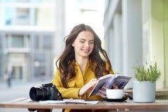 Lycklig kvinna med handboken som dricker kakao på stadskafét royaltyfri fotografi