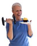 Lycklig kvinna med hanteln och muffin Fotografering för Bildbyråer