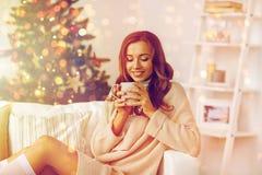 Lycklig kvinna med kopp te som är hemmastadd för jul Royaltyfri Foto