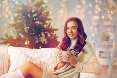 Lycklig kvinna med kopp te som är hemmastadd för jul Royaltyfri Fotografi
