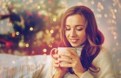 Lycklig kvinna med kopp te som är hemmastadd för jul Royaltyfri Bild