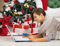 Lycklig kvinna med kreditkorten genom att använda bärbara datorn nära julträd Arkivfoto