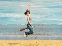 Lycklig kvinna med kvastbanhoppning på stranden royaltyfria foton