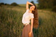 Lycklig kvinna med långt hår i aftonen Royaltyfri Foto