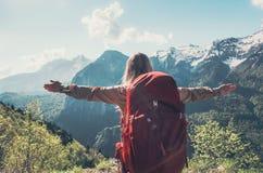 Lycklig kvinna med lyftt resande för ryggsäck händer arkivfoton