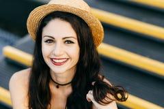 Lycklig kvinna med mörkt lyxigt hår, charmiga ljusa ögon, brunn-formade röda kanter och ren hud som trycker på med handen hennes  royaltyfri bild