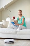 Lycklig kvinna med minnestavlaPC som hemma dricker te Royaltyfria Foton