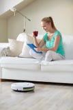 Lycklig kvinna med minnestavlaPC som hemma dricker te Arkivfoton