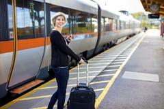 Lycklig kvinna med mobiltelefonen och bagage på drevstationen royaltyfria bilder
