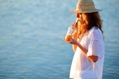 Lycklig kvinna med orange fruktsaft i disponibel kopp mot havet arkivbilder