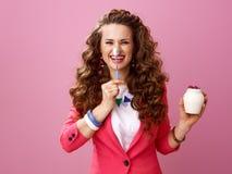 Lycklig kvinna med organisk yoghurt för lantgård och sked som har rolig tid Arkivfoton
