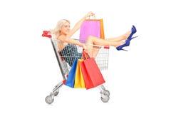 Lycklig kvinna med påsar som sitter i en shoppingvagn Fotografering för Bildbyråer
