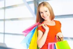 Lycklig kvinna med påsen på en shopping i galleria arkivbilder
