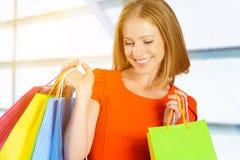 Lycklig kvinna med påsen på en shopping i galleria arkivfoton