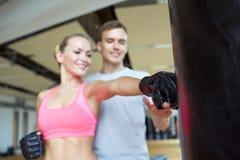 Lycklig kvinna med personlig instruktörboxning i idrottshall Arkivbilder
