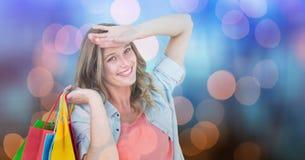 Lycklig kvinna med shoppingpåsar över bokeh Arkivbild
