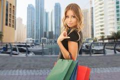 Lycklig kvinna med shoppingpåsar över den dubai staden arkivbilder