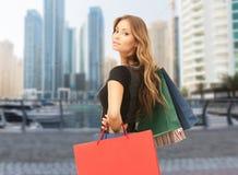 Lycklig kvinna med shoppingpåsar över den dubai staden royaltyfri fotografi